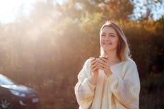 Bella donna piena d'ammirazione che beve tè caldo dalla tazza del termos immagini stock libere da diritti