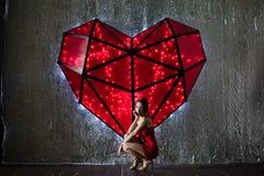 Bella donna in poco vestito rosso con il cuore del biglietto di S. Valentino Fotografia Stock Libera da Diritti