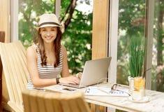 Bella donna positiva che per mezzo del computer portatile Fotografie Stock