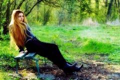Bella donna premurosa che si distende sul banco di sosta Fotografia Stock Libera da Diritti