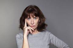 Bella donna premurosa 50s nella riflessione Fotografia Stock