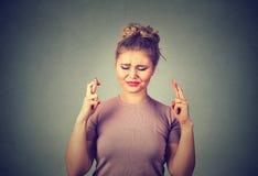 Bella donna promettente che attraversa le sue dita, occhi chiusi, sperando, chiedendo il più bene Fotografie Stock Libere da Diritti