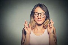 Bella donna promettente che attraversa le sue dita, occhi chiusi, speranti fotografia stock libera da diritti