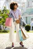 Bella donna riccia che ha manciate di sacchetti della spesa fotografia stock libera da diritti