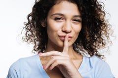 Bella donna riccia che preme le dita alle sue labbra fotografia stock libera da diritti