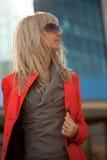 Bella donna in rivestimento rosso che cammina nella città Fotografie Stock