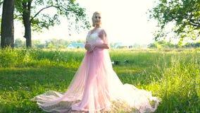 Bella donna romantica in vestito rosa-chiaro che posa in una bellezza della foresta di mattina, modo video d archivio