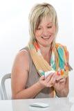 Bella donna senior all'ufficio facendo uso di un cellulare Fotografie Stock Libere da Diritti