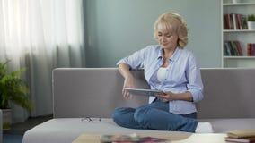 Bella donna senior bionda che si siede sul sofà e che fa scorrere sulla compressa, apps archivi video