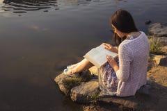 Bella donna senior castana che studia per i suoi esami che si siedono o Fotografia Stock