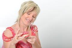Bella donna senior in vestito rosa che mangia maca giallo e rosa Immagini Stock