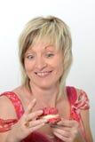 Bella donna senior in vestito rosa che mangia maca giallo e rosa Immagine Stock Libera da Diritti