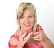 Bella donna senior in vestito rosa che mangia maca giallo e rosa Fotografia Stock