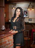 Bella donna sensuale che sta con il bicchiere di vino sul camino dei mattoni rossi Immagini Stock