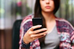 Bella donna seria che per mezzo dello smartphone Fotografia Stock