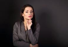 Bella donna seria di affari in vestito grigio che pensa sul g scuro Fotografie Stock Libere da Diritti