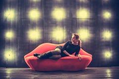 Bella donna sexy alla moda di lusso sul sofà rosso delle labbra il backgound delle luci Immagini Stock Libere da Diritti