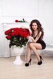 Bella donna sexy con il mazzo delle rose rosse in apartmen interni Immagini Stock Libere da Diritti
