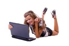 Bella donna sexy con un computer portatile che si trova sul pavimento. Immagini Stock