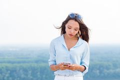 Bella donna sexy sensuale con lo smartphone a disposizione in natura fotografia stock libera da diritti