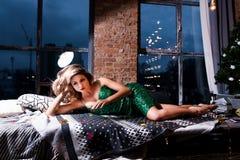 Bella donna sexy in vestito scintillante verde elegante che si trova sul sofà moderno Modello di moda con le gambe lunghe che pos immagini stock