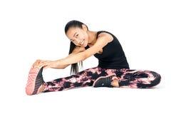 Bella donna sorridente asiatica che fa allungamento sedendosi la sua gamba Immagine Stock Libera da Diritti