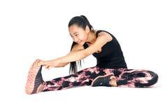 Bella donna sorridente asiatica che fa allungamento sedendosi la sua gamba Immagine Stock