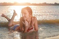 Bella donna sorridente in bikini che si trova su una spiaggia Immagine Stock