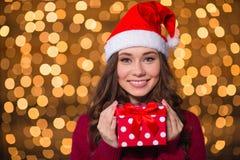 Bella donna sorridente in cappello del Babbo Natale con il piccolo regalo Immagine Stock