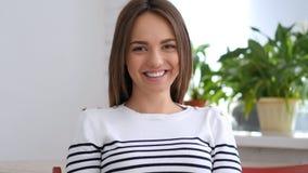 Bella donna sorridente che esamina macchina fotografica in ufficio Immagine Stock Libera da Diritti
