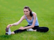 Bella donna sorridente che fa allungando esercizio sull'erba nel parco Fotografia Stock Libera da Diritti
