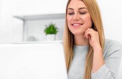 Bella donna sorridente che lavora ad un computer portatile a casa o nell'ufficio Fotografie Stock