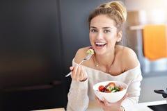 Bella donna sorridente che mangia insalata vegetariana organica fresca in cucina moderna fotografia stock