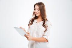 Bella donna sorridente che per mezzo del computer della compressa Immagini Stock Libere da Diritti