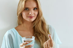 Bella donna sorridente che prende la pillola della vitamina Supplemento dietetico Immagine Stock