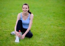 Bella donna sorridente che si rilassa sull'erba nel parco immagine stock