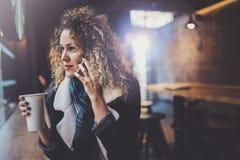 Bella donna sorridente che si siede al caffè urbano e che parla con gli amici tramite smartphone mobile Ritratto casuale di abbas Immagine Stock Libera da Diritti