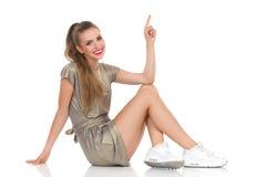 Bella donna sorridente che si siede su un pavimento e che indica su immagine stock libera da diritti