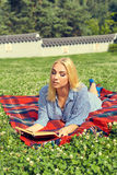Bella donna sorridente che si trova su un'erba all'aperto Immagini Stock Libere da Diritti