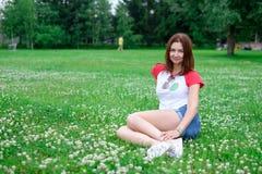 Bella donna sorridente che si trova su un'erba all'aperto Fotografia Stock Libera da Diritti