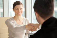 Bella donna sorridente che stringe mano maschio, arrivante al lavoro inter immagini stock