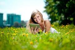 Bella donna sorridente con il pc del ridurre in pani, all'aperto Fotografia Stock