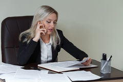 Bella donna sorridente di affari che lavora alla sua scrivania con i documenti e che parla sul telefono Fotografia Stock