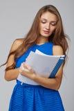 Bella donna sorridente di affari, con i documenti, su una parte posteriore di gray Immagini Stock Libere da Diritti