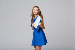 Bella donna sorridente di affari, con i documenti, su una parte posteriore di gray Immagine Stock Libera da Diritti