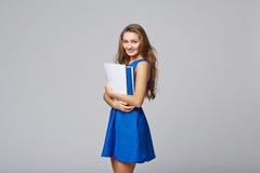 Bella donna sorridente di affari, con i documenti, su una parte posteriore di gray Fotografia Stock