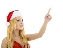 Bella donna sorridente di Santa di natale che indica sulla mostra della copia Fotografia Stock