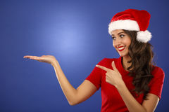 Bella donna sorridente di Santa di natale che indica sulla mostra della copia Fotografie Stock Libere da Diritti