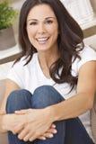 Bella donna sorridente felice che si siede sul sofà Immagini Stock