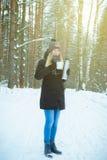 Bella donna sorridente felice con una tazza dell'inverno sulla via di sorriso di godimento della ragazza bevanda calda all'aperto Immagine Stock